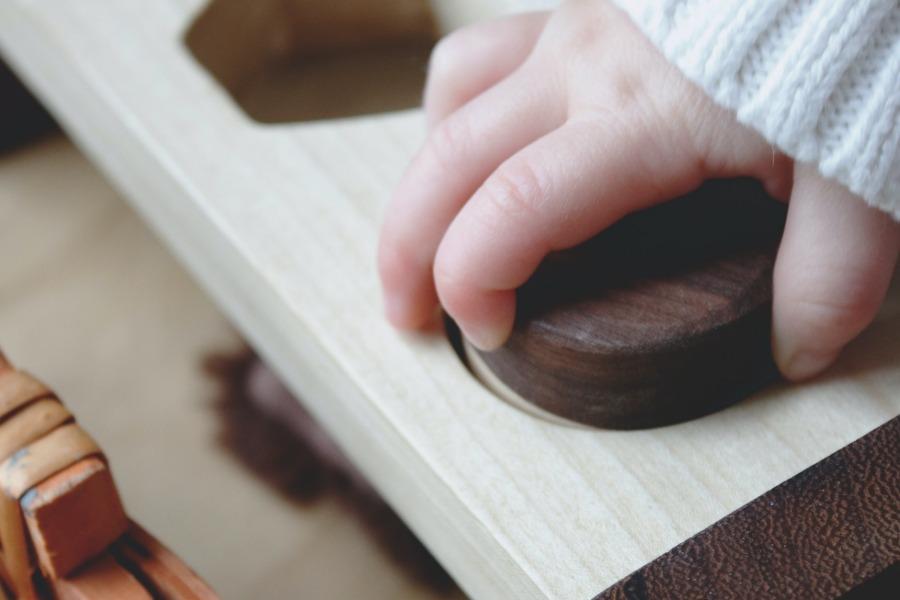main d'enfant plaçant qui développe son autonomie avec un jeu montessori