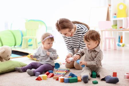 une babysitter jouant avec deux enfants assis par terre pendant son job étudiant