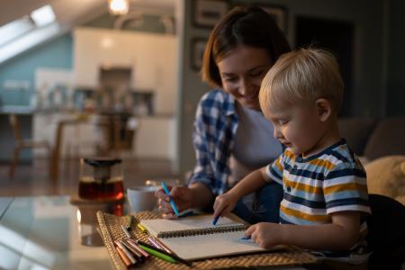 Une babysitter et un enfant qui dessine dans un cahier lors d'un babysitting