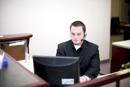 Homme installé à un bureau devant son ordinateur, avec un micro pendant son job étudiant