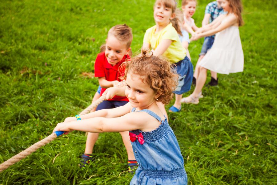 jeu de tire à la corde : les bienfaits du sport. Il y a plusieurs enfants en train de jouer au tire à la corde sur l'herbe