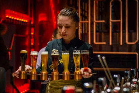 jeune fille tenant un plateau rempli de verres comme serveuse pour son job étudiant