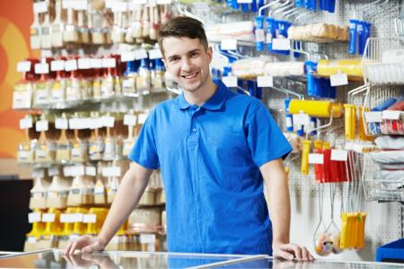 Vendeur se tenant debout devant un rayon d'outils de bricolage lors de son job étudiant