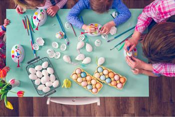 une famille décore les œufs de pâques