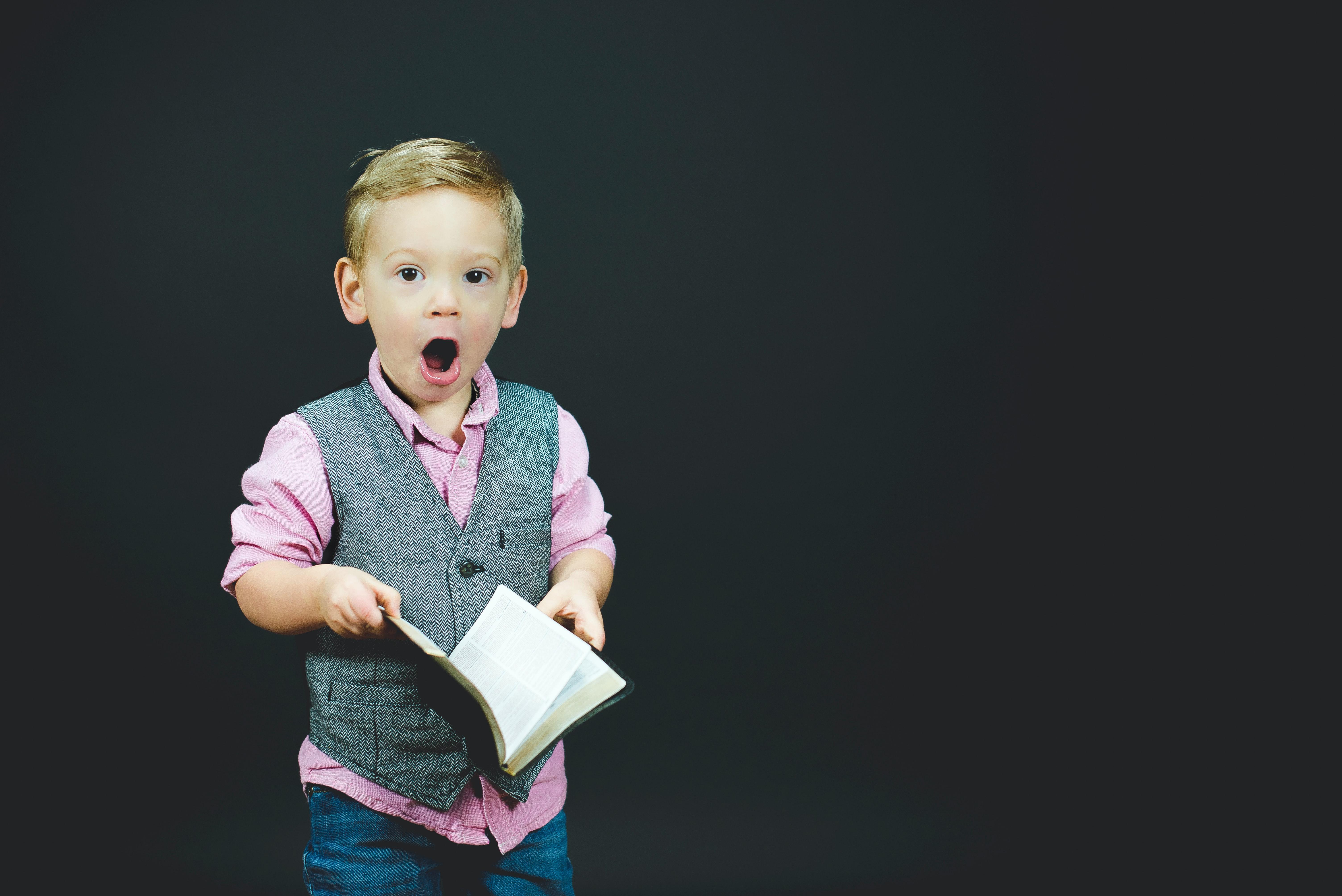 Un enfant avec un livre étonné des idées reçu sur les écoles Montessori